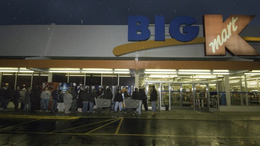 Kmart's plan to be open for 41 straight hours beginning at 6 a.m. Thanksgiving morning is drawing criticism. At this Kmart store in Connecticut, shoppers wait in line to take advantage of sales on Thanksgiving Day.