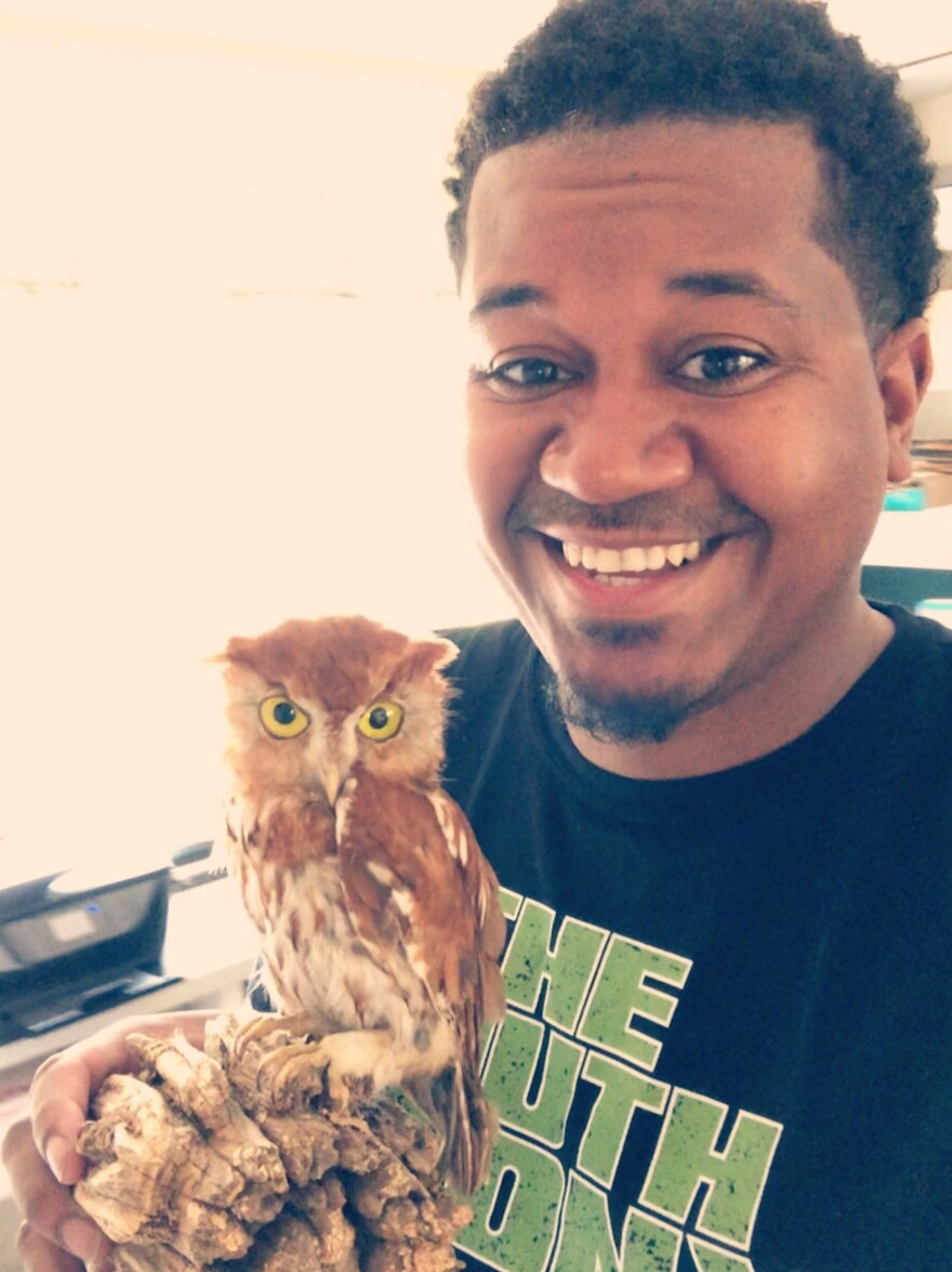 Jason Ward holds a taxidermy screech owl.