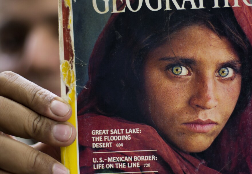The owner of a bookstore shows a copy of <em>National Geographic</em> magazine with the photograph of Sharbat Gula, when she was around 12 years old.