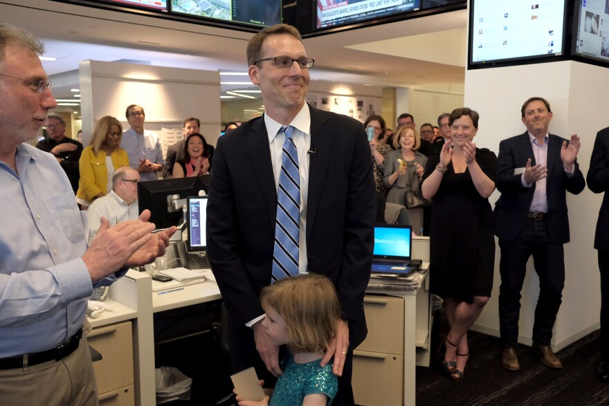<em>The Washington Post</em>'s David Fahrenthold (center) learns he won the 2017 Pulitzer Prize for national reporting, surrounded by his colleagues in the newsroom Monday.