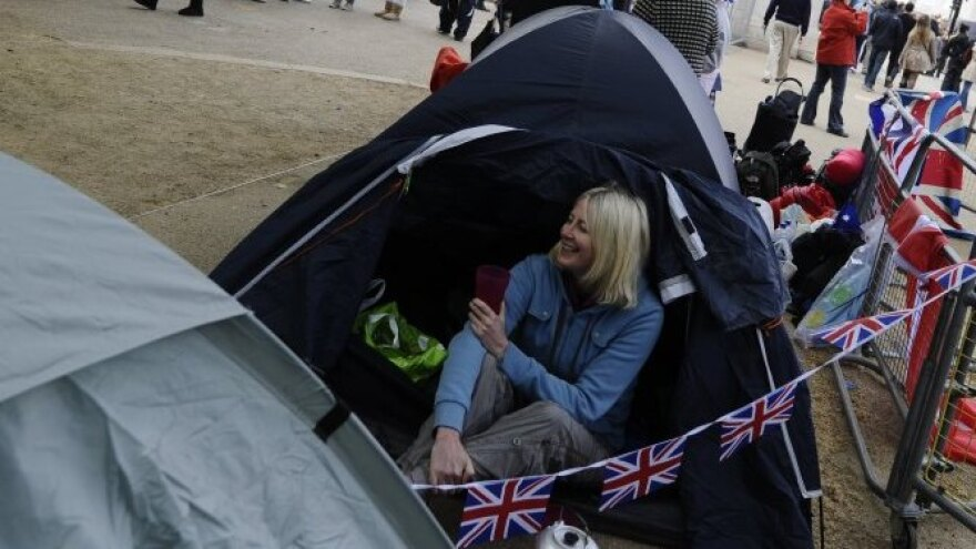 People sit on the Mall as they reserve their space prior to the Royal Wedding tomorrow.