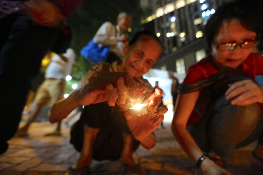 A woman lights candles in memory of Lee Kuan Yew at a community center in Singapore. Lee, Singapore's first premier, died Monday at the age of 91.