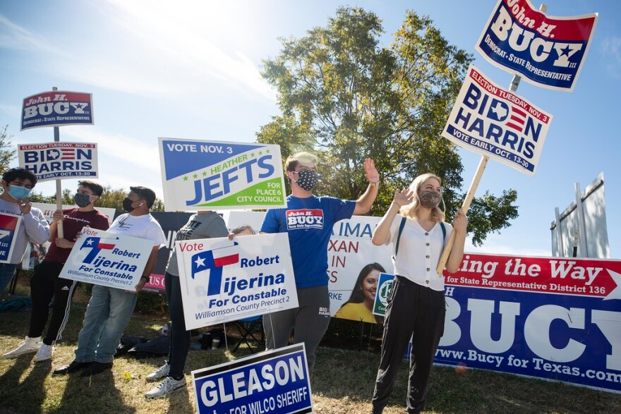 Supporters of candidates on the ballot in Williamson County wave to voters at a polling site in Cedar Park on Tuesday.