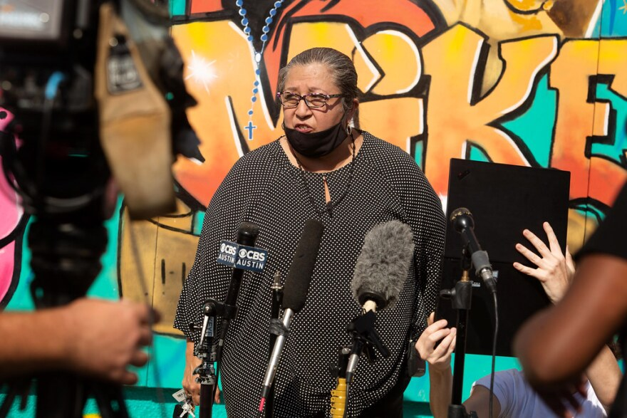 Brenda Ramos speaks to a gaggle of reporters in front of a mural honoring her son.