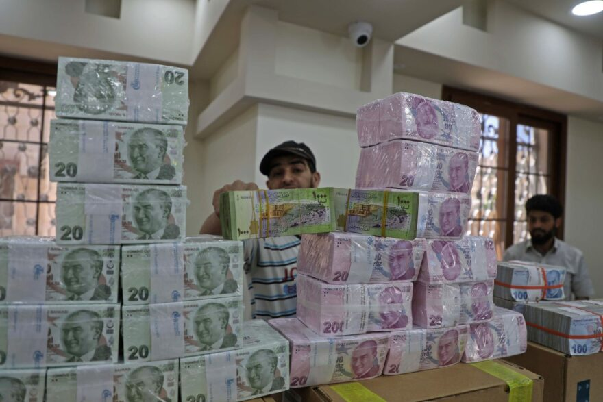 An employee sorts Turkish lira banknotes at a bank in the town of Sarmada in Syria's northwestern Idlib province. Authorities in northwest Syria are taking steps to substitute the plummeting Syrian pound with the Turkish lira to shield their opposition-held region from an economic crisis ahead of new US sanctions, an official said.