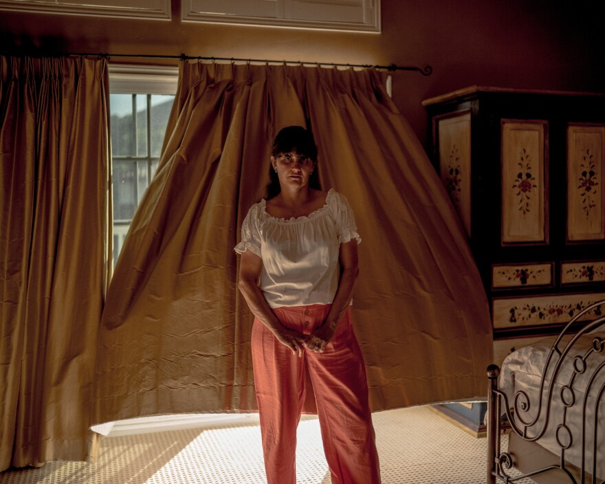 """After making a new life in the U.S., Jacob Moscovitch's mother, or Imma, raised three kids and led the household while working a part-time job. Moscovitch says his older sister Simone told him, """"Imma is my superhero, no cape necessary."""" Here, Imma stands for a portrait in her bedroom on May 8."""