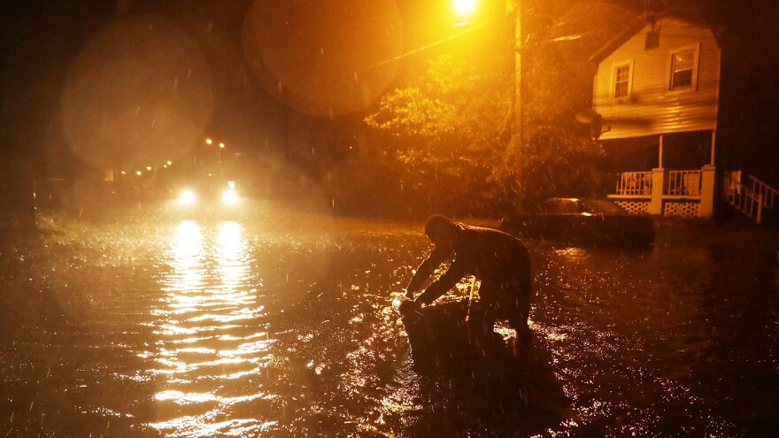 Michael Nelson floats in a boat made from a metal tub and fishing floats after the Neuse River went over its banks and started to flood his street in New Bern, N.C., on Thursday.
