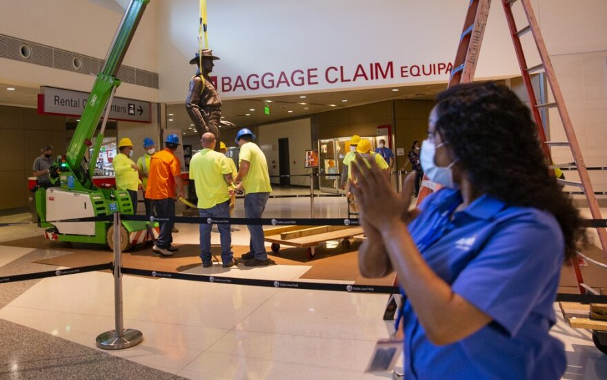 """Tiffany Anderson claps as a crew removes the Texas Ranger """"One Riot, One Ranger"""" statue by Waldine Tauch from the main lobby inside Love Field airport Thursday."""