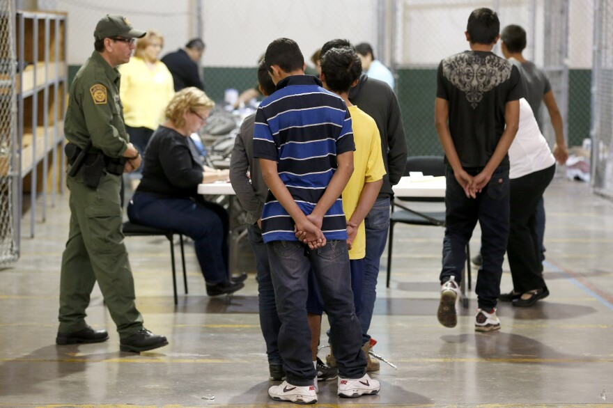Boys wait in line to make a phone call at the U.S. Customs and Border Protection Nogales Placement Center in Arizona in June. Many of the minors who arrived from Central America last year are now awaiting court hearings to determine if they can stay in the U.S.