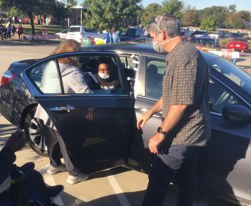 Photo of an election worker, voter Lisa Jackson in the backseat of the car, and driver Yair Brama.