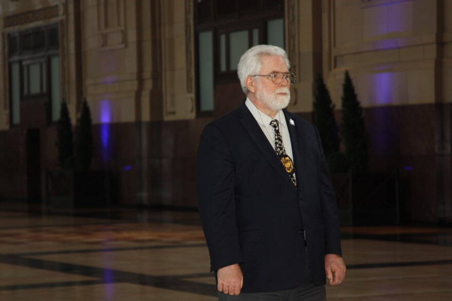 Dr. Rex Archer in dark suit and tie standing in the Great Hall at Union Station in Kansas City, Missouri