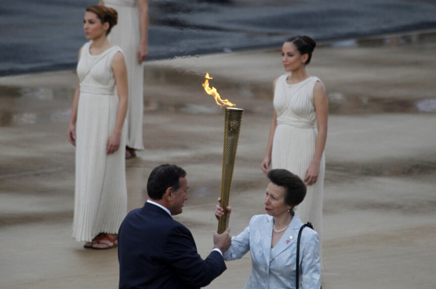 President of the Greek Olympic Committee Spyros Kapralos passes the torch to Britain's Princess Anne, right.