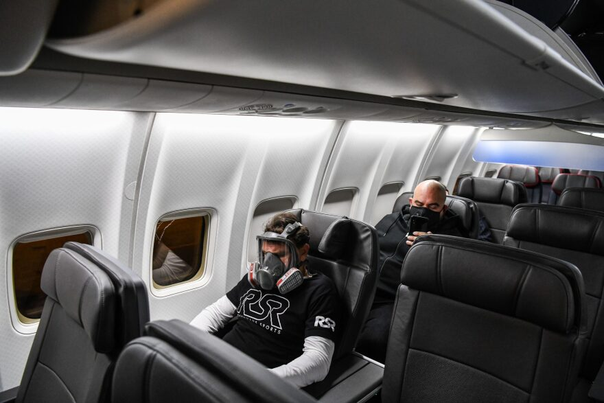A man wears a gasmask as he travels in a flight from Miami to Atlanta in Miami, on April 23, 2020. (CHANDAN KHANNA/AFP via Getty Images)