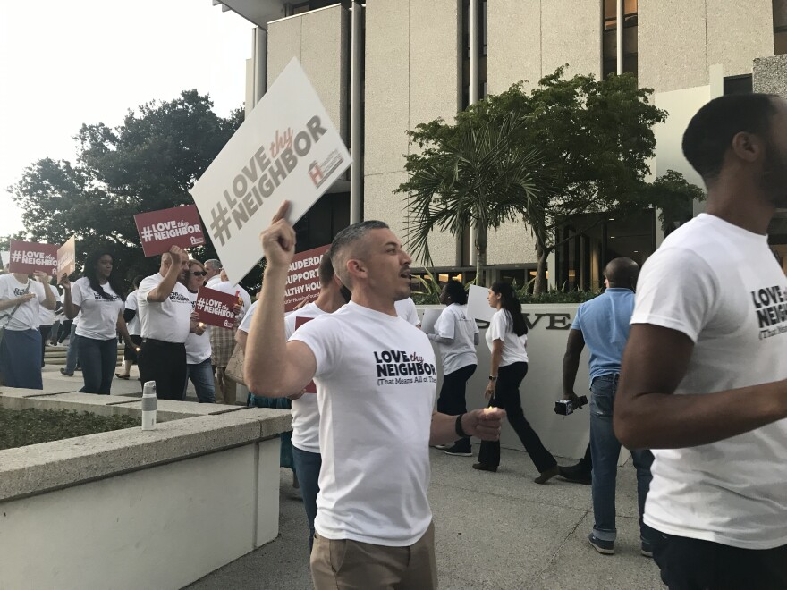 AIDS Healthcare Foundation bussed supporters from its Fort Lauderdale campus to city hall Monday, to rally just before the 6 p.m. community meeting.