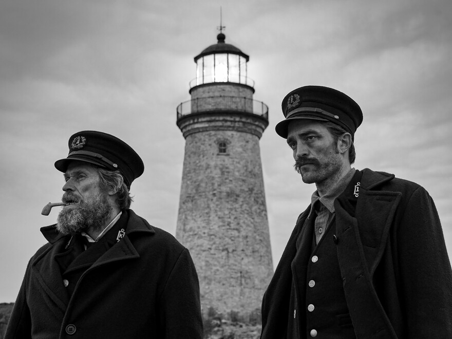 Williem Dafoe, left, and Robert Pattinson are stranded during a bad storm in <em>The Lighthouse.</em>