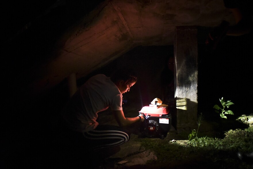 In this Dec. 21, 2017 filw photo, barrio Patron resident Karina Santiago Gonzalez works on a small power plant in Morovis, Puerto Rico.