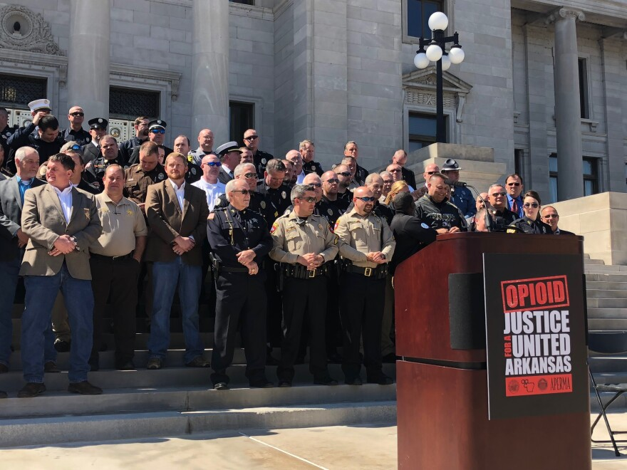 Representatives from law enforcement agencies across Arkansas gather at the Capitol to announce a new lawsuit targeting opioid manufacturers.