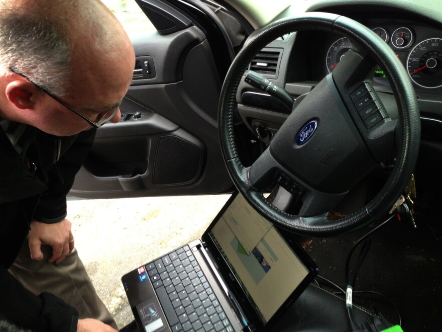 "Detective Dave Wells plugs his laptop into a car's event data recorder. A large portion of new cars are equipped with the device, and the government is considering making them mandatory in all vehicles. But some say there should be an ""off"" option."