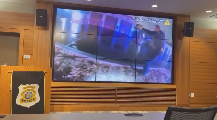Photo of a room with a large screen where the body cam footage shows an officer with a gun raised