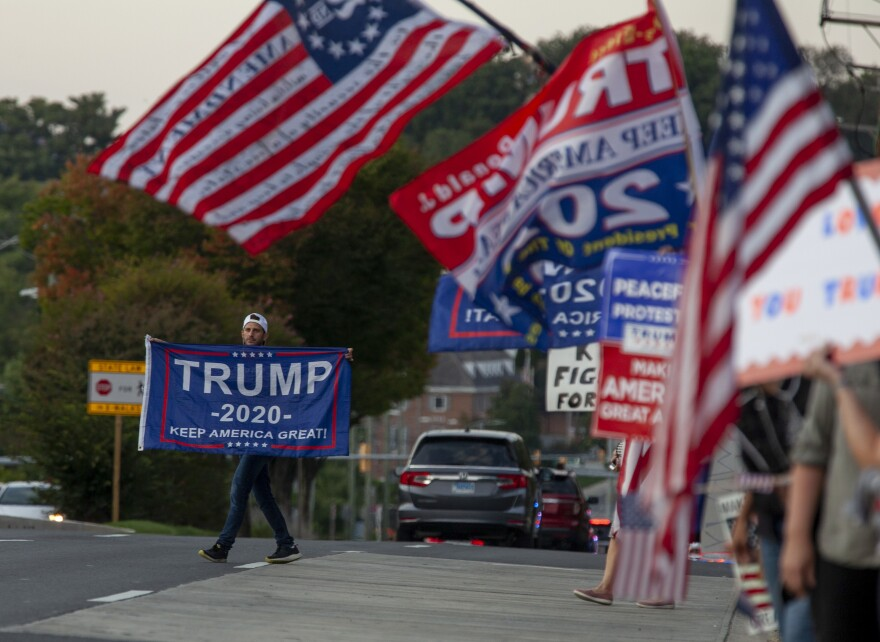 A Trump supporter carries his flag into the street just outside of Walter Reed Medical Center.