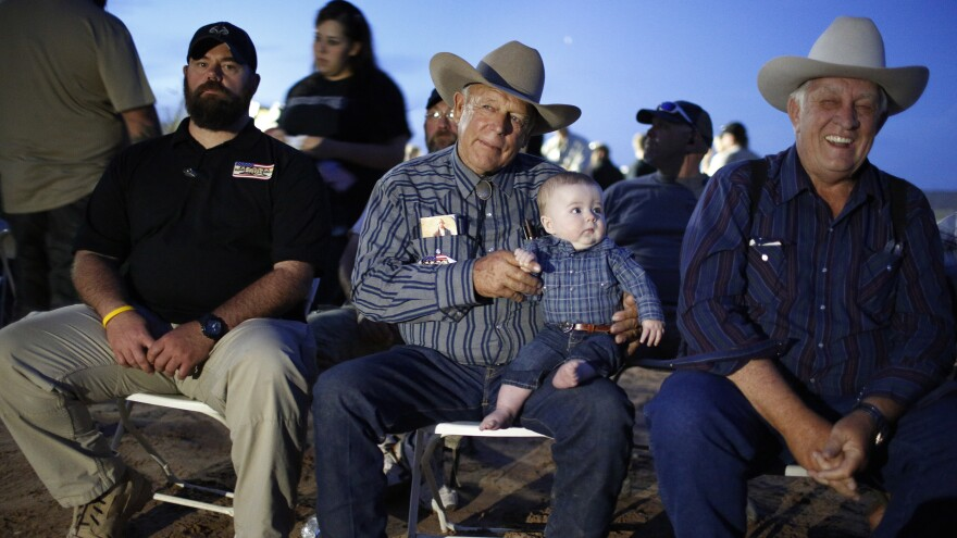 Rancher Cliven Bundy holds his 5-month-old grandson Roper Cox on Saturday in Bunkerville, Nev. Bundy was hosting an event to mark one year since the Bureau of Land Management's failed attempt to collect his cattle.