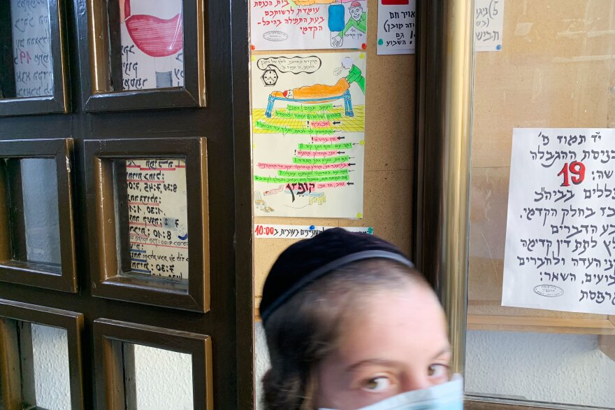 A young worshiper passes the signs and cartoons Yehezkel Cahn has tacked up at the entrance to the small synagogue. The number 19 in red (at right) indicates the maximum number of worshipers allowed indoors, per Israeli government guidelines at the time.