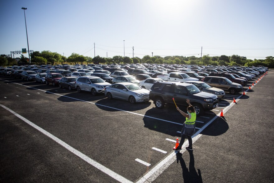 A worker directs traffic lining up for food from the Central Texas Food Bank at the Toney Burger Center in South Austin on April 30.