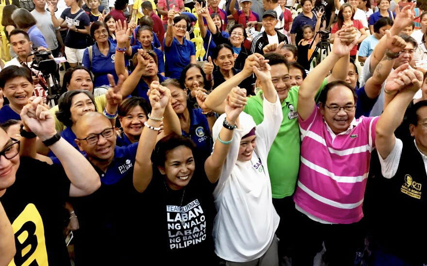 "Opposition senatorial candidates known as ""Otso Diretso"" or the ""Straight Eight"" take a group photo with a crowd of civic leaders inside the St. Ferdinand Cathedral in Lucena, Philippines."
