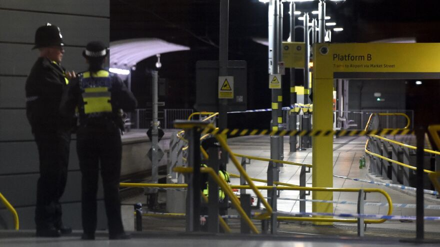 Police stand near a cordon at Manchester Victoria Station on Tuesday after an attack on New Year's Eve sent three people to the hospital with knife injuries.