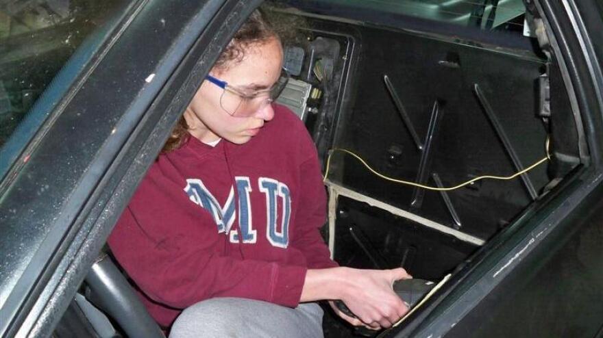 14-year-old Kathryn DiMaria drilling door rivets in her Pontiac Fiero.