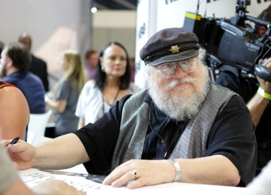 <em>Game of Thrones</em> author George R.R. Martin signs autographs during the 2014 Comic-Con International Convention at the San Diego Convention Center.