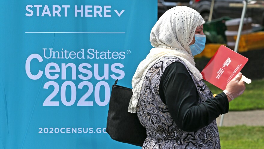 A woman uses a fan to cool off while waiting by a 2020 census booth at a farmer's market in Everett, Mass., north of Boston, in July. Concerns about the accuracy of the data after Trump officials cut the count short have led to calls for a redo.