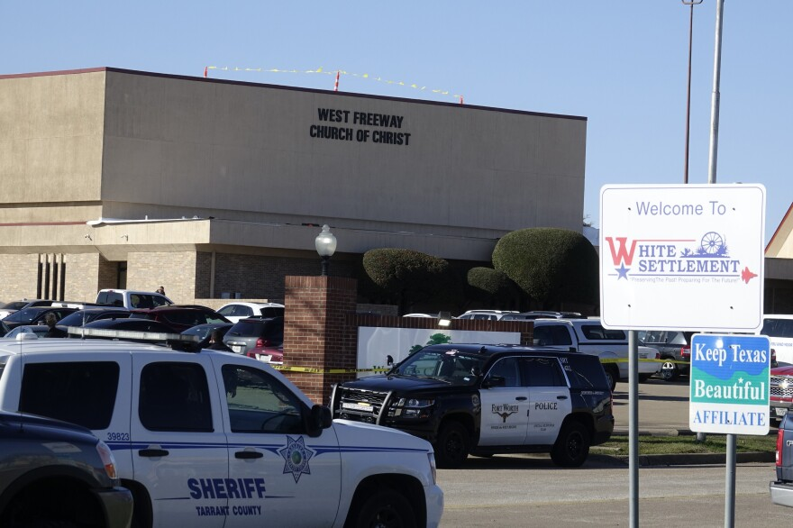 Law enforcement vehicles are seen parked outside West Freeway Church of Christ as authorities continue to investigate a fatal shooting at the church on Sunday, in White Settlement, Texas.