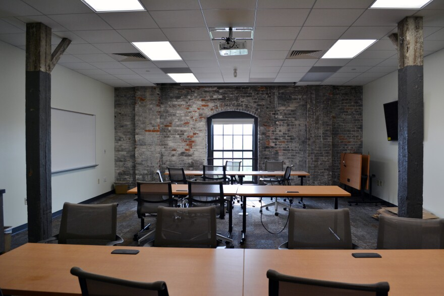 Fourth floor staff conference room with exposed brick and wood columns, and ceiling tile and carpet for acoustics. dayton metro library