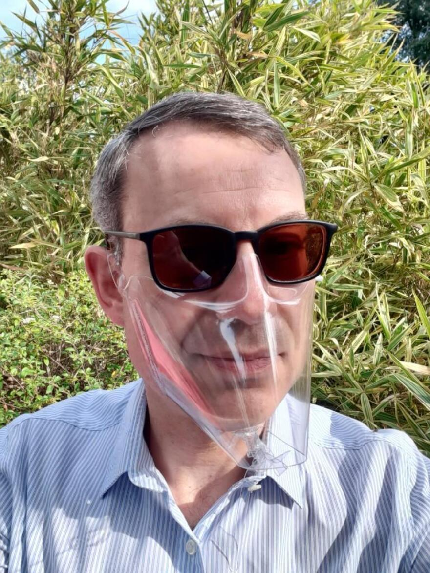 Christophe Bertrand wears an inexpensive mask made of a single plastic sheet, manufactured by his Simon company.