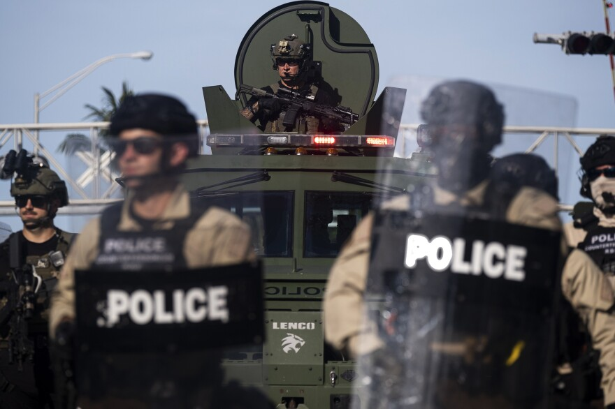 A Miami police officer watches protesters from an armored vehicle during a rally in Miami on Sunday. Thousands of National Guard troops patrolled major U.S. cities after five consecutive nights of protests.