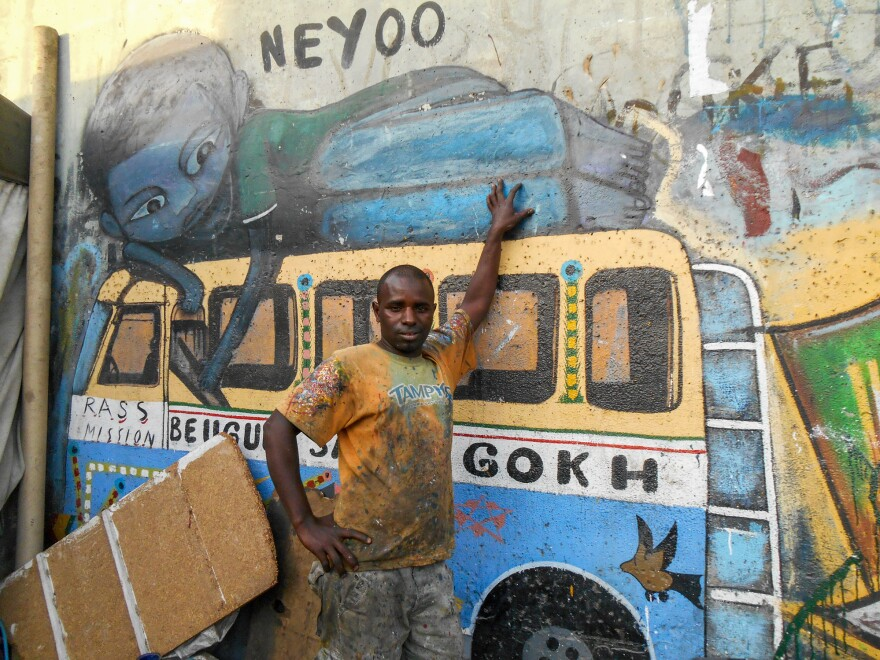 """Kalidou Diallo, aka """"Neyoo,"""" is a car rapide painter who also does murals, like the one behind the bus."""