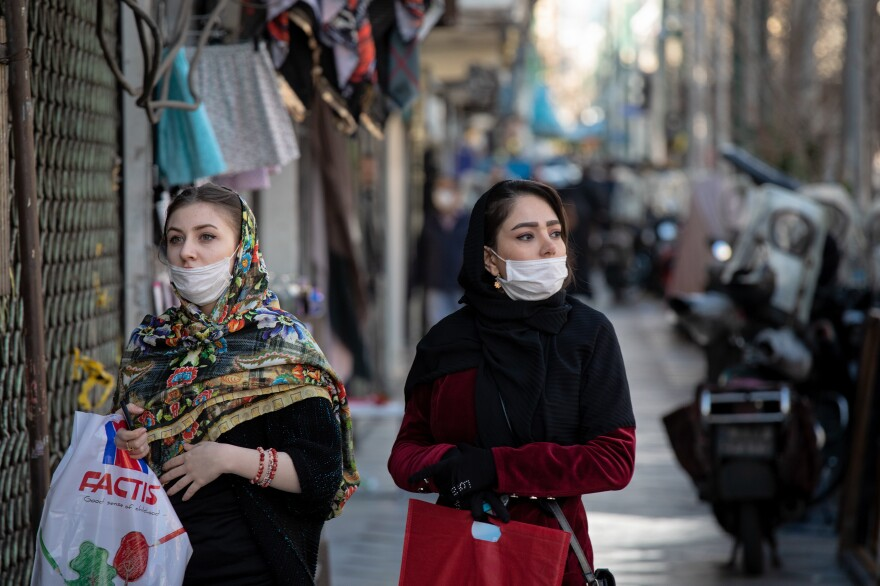 Wearing masks that cover their mouths, but not their noses, two young women walk through Tehran's Valiasr street after shopping. Under normal circumstances, the Valiasr promenade, famous for its medium budget boutiques, would be packed.
