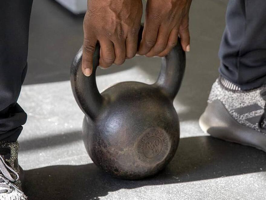 Justice Williams demonstrates how to lift a kettlebell.