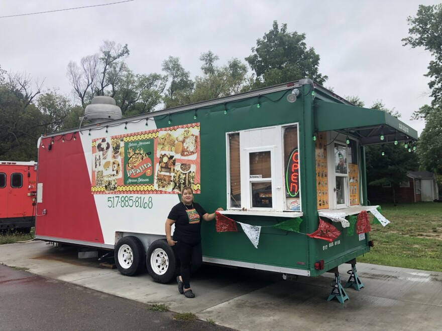 """Eva González está parada afuera del camión de comida La Fajita.  El carrito de comida es del color de la bandera mexicana (rojo, blanco y verde).  Hay dos ventanas al costado y al frente del camión.  ese """"Abierto"""" El letrero de neón se puede ver a través de la ventana lateral.  El picado mexicano cuelga de repisas de madera afuera de las ventanas."""