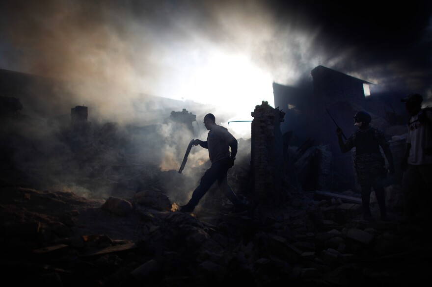 A man carries a shotgun as he walks through a collapsed burning building while trying to keep looters at bay in the commercial district of downtown Port-au-Prince.