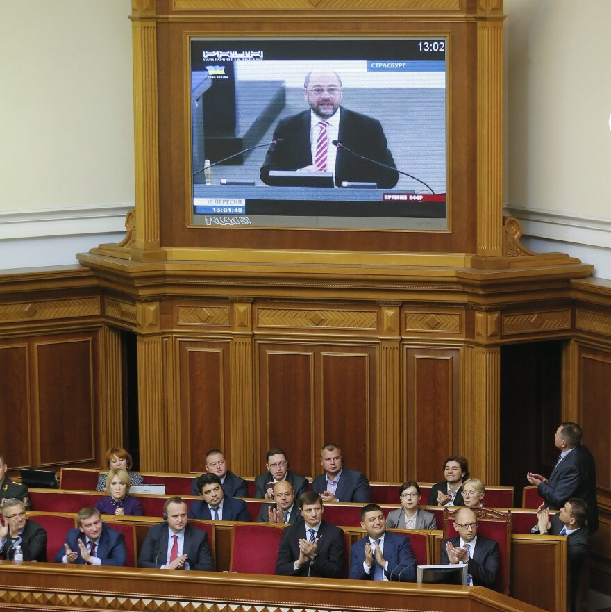 Ukrainian lawmakers applaud a televised address by the President of the European Parliament Martin Schulz (on screen) in the Ukrainian parliament on Tuesday in Kiev. The parliament voted to strengthen trade ties with the EU, but not until 2016.
