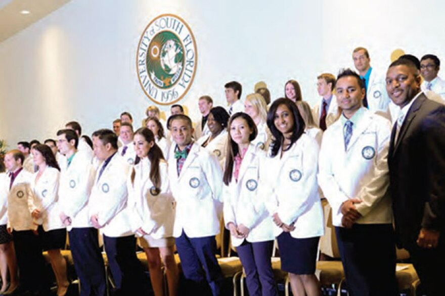 Kevin Sneed (far right), dean of the USF Health College of Pharmacy, stands with students at a White Coat Ceremony.