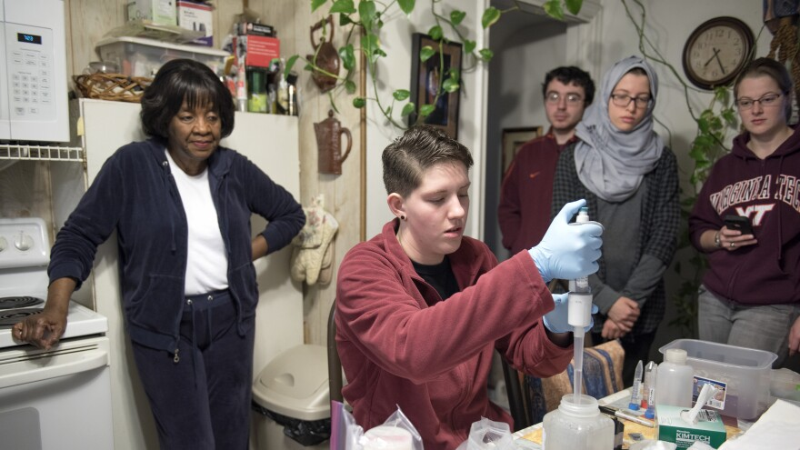 Virginia Tech students from professor Marc Edwards' lab and other student volunteers work on a second round of water testing for lead contamination in Elnora Carthan's home in Flint, Mich. Maggie Carolan is working with samples at the table.