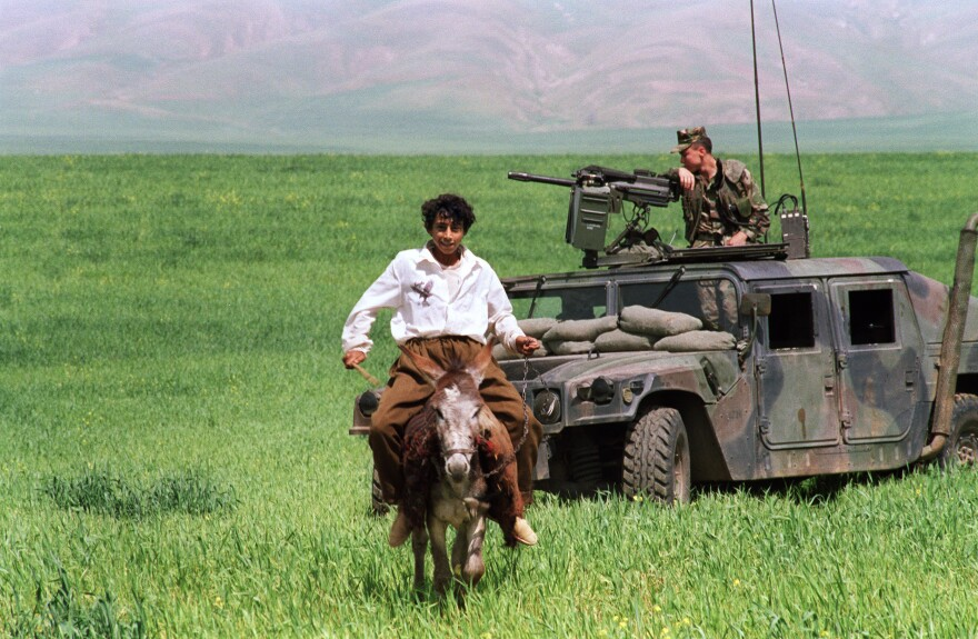 An Iraqi Kurdish boy rides a donkey in 1991 near Zakho, in northern Iraq. A U.S. Marine, part of the contingent to protect the Kurds from Iraq's army, looks on.