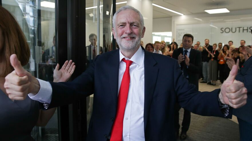 Labour leader Jeremy Corbyn gives a thumbs up as he arrives at the party's headquarters in London on Friday. Corbyn says he's prepared to keep up the pressure as Theresa May works to form a new government in the U.K.