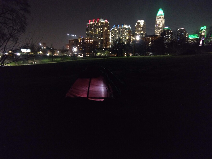 A homeless resident uses a flashlight in a tent at a homeless camp near uptown Charlotte.