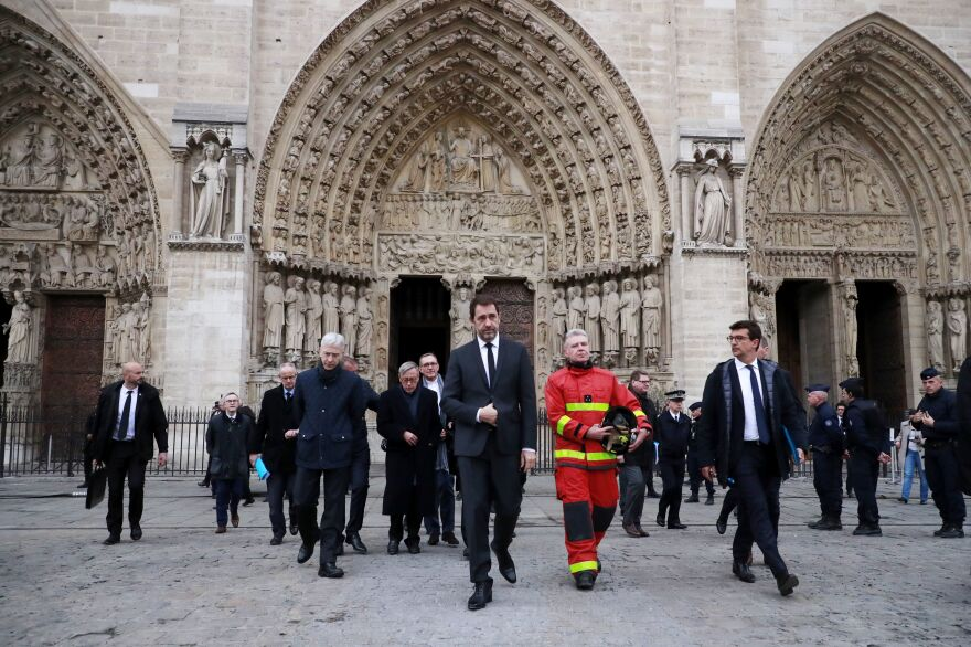 French Interior Minister Christophe Castaner (center) and Paris Fire Brigade Commander General Jean-Claude Gallet (center right) exit the Notre Dame Cathedral. French investigators probing the devastating blaze questioned workers who were renovating the monument.
