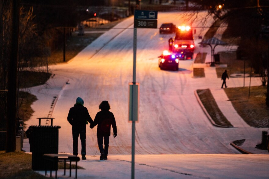 Pedestrians walk through snow in the Travis Heights neighborhood of South Austin on Sunday.