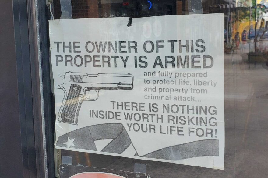 Signs in the window of a bar in downtown Graham, N.C.